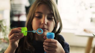 A small girl blowing bubbles at home. Close up