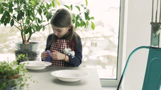 A small girl setting the table at home.