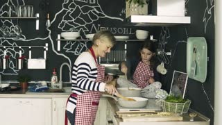 A small girl with grandmother at home, cooking. Family and generations concept.