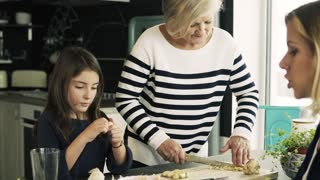 A small girl with her mother and grandmother at home, cooking. Family and generations concept.