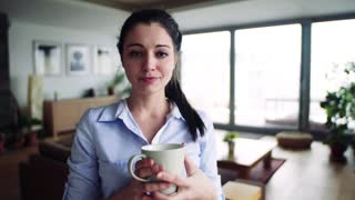 A woman standing in the living room, holding a cup of coffee. Smart home control system.