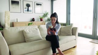 A woman with tablet and a cup of coffee in the living room. Smart home control system.