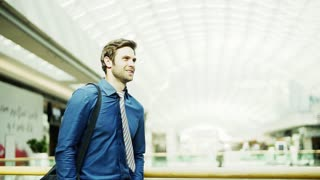 A young businessman with a bag walking inside a big building. Copy space. Slow motion.
