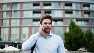 A young businessman with a smartphone walking on a bridge, making a phone call.