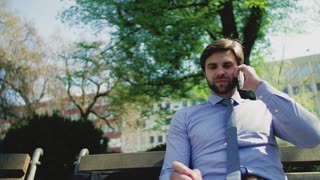 A young businessman with smartphone outside in city, sitting on a bench, making a phone call and writing.