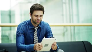 A young businessman with tablet sitting on a bench in a modern building. Copy space. Slow motion.