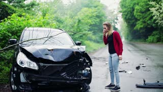 A young frustrated woman making a phone call after a car accident, kicking in anger. Slow motion.