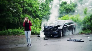 A young frustrated woman making a phone call after a car accident, smoke in the background. Slow motion.