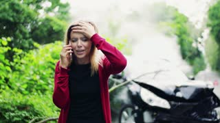 A young frustrated woman making a phone call after a car accident, smoke in the background.