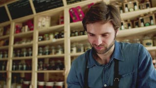 A young man shop assistant working in a zero-waste store or shop. Green living.