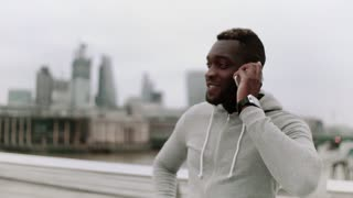 A young sporty black man runner with smartphone standing on the bridge in a city, making a phone call.