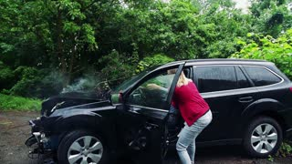 A young woman helping a mature man to get out of the crashed car after an accident. Slow motion.