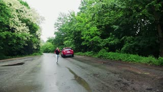 A young woman running towards the crashed car after an accident. Slow motion.