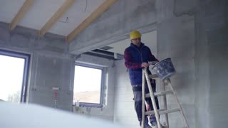 Accident of a male worker at the construction site. A man falling off the ladder. Slow motion.