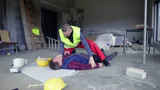 Accident of a male worker at the construction site. A man helping his colleague lying unconscious on the floor. Slow motion.