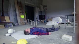 Accident of a male worker at the construction site. A man helping his colleague lying unconscious on the floor.
