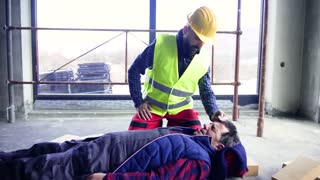Accident of a male worker at the construction site. A man helping his injured colleague.
