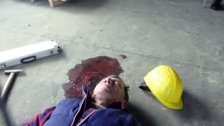 Accident of a male worker at the construction site. A man lying unconscious on the floor. Close up.