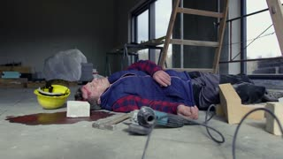 Accident of a male worker at the construction site. A man lying unconscious on the floor.