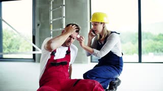 Accident of a male worker at the construction site. A woman with smartphone helping her injured colleague, calling and ambulance and wiping his forehead. Slow motion.
