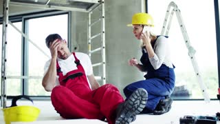 Accident of a male worker at the construction site. A woman with smartphone helping her injured colleague, calling and ambulance and wiping his forehead.