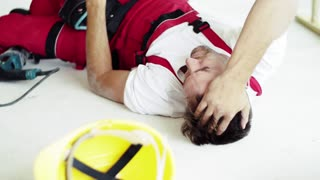 Accident of a male worker at the construction site. An injured man lying on the floor, holding his head.