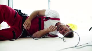 Accident of a male worker at the construction site. An injured man lying on the floor, holding his shoulder. Slow motion.