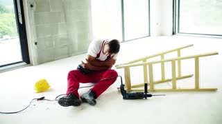 Accident of a male worker at the construction site. An injured man sitting on the floor, holding his arm. Slow motion.