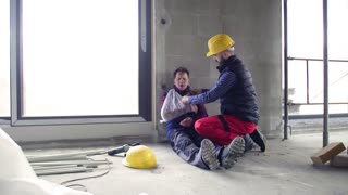 Accident of man workers at the construction site. A builder with a broken arm.