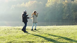 Active senior couple on a walk in a beautiful autumn nature. A man and woman by the lake in the early morning.