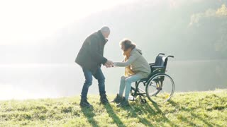 Active senior couple on a walk in a beautiful autumn nature. A man and woman in a wheelchair by the lake in the early morning. A man is helping a woman to stand up. Slow motion.