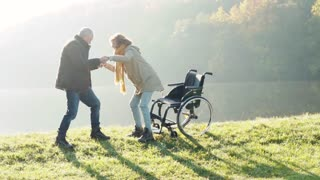Active senior couple on a walk in a beautiful autumn nature. A man and woman in a wheelchair by the lake in the early morning. A man is helping a woman to walk. Slow motion