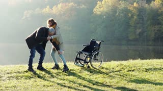 Active senior couple on a walk in a beautiful autumn nature. A man and woman in a wheelchair by the lake in the early morning. A man is helping a woman to walk. Slow motion.