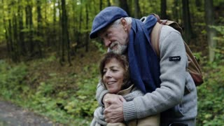 Active senior couple on a walk in a beautiful autumn nature. A man and woman in a wheelchair in forest. Slow motion.
