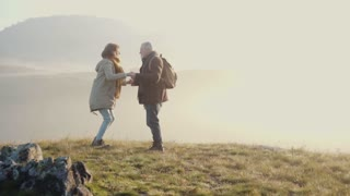 Active senior couple on a walk in a beautiful autumn nature. A man and woman jumping. Slow motion.