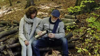 Active senior couple on a walk in a beautiful autumn nature. A man pouring a hot drink, a woman drinking tea or coffee.