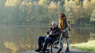 Active senior couple on a walk in a beautiful autumn nature. A woman and man in a wheelchair by the lake in the early morning. Slow motion