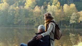 Active senior couple on a walk in a beautiful autumn nature. A woman and man in a wheelchair by the lake in the early morning. Slow motion.