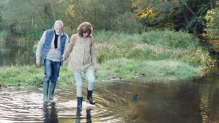 Active senior couple on a walk in a beautiful autumn nature. A woman and man walking in water in the early morning. Slow motion.