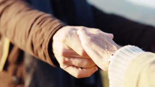Active senior couple on a walk in a beautiful autumn nature, hugging. Slow motion.