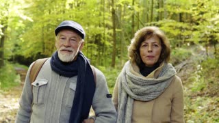 Active senior couple on a walk in a beautiful autumn nature. Slow motion.