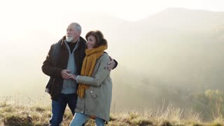 Active senior couple on a walk in a beautiful autumn nature. Slow motion