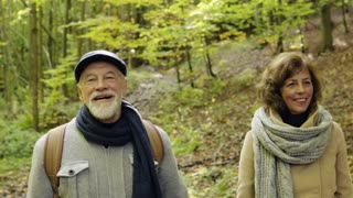 Active senior couple on a walk in a beautiful autumn nature
