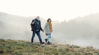 Active senior couple with binoculars on a walk in a beautiful autumn nature. Slow motion.