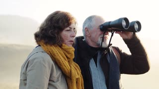 Active senior couple with binoculars on a walk in a beautiful autumn nature.