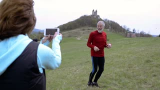 Active senior runners in nature taking photo with smart phone.