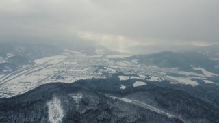 Aerial view of town with hills in winter.