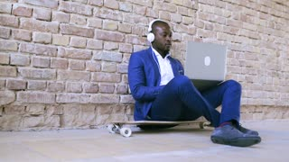 African businessman with laptop and headphones.