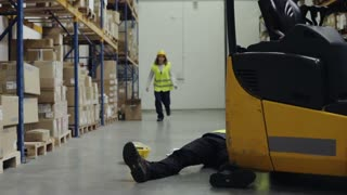 An accident in a warehouse. Woman running towards her colleague lying on the floor next to a forklift. Slow motion