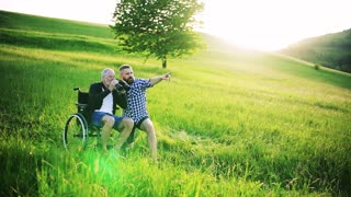 An adult hipster son and senior father in wheelchair using binoculars at sunset in nature. Slow motion.